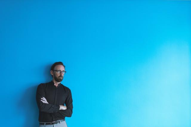 Thoughtful male executive standing against blue wall in office