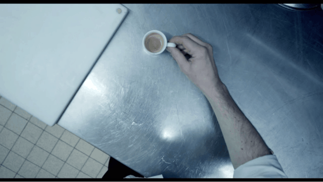 Man's hand holding cup of coffee from his point-of-view