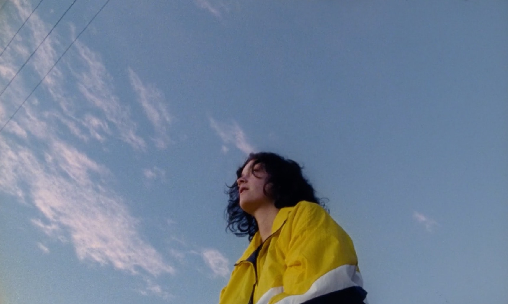 A girl standing in a colourful jacket under the sky