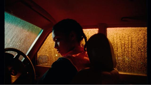 A girl sitting in th car at rainy night