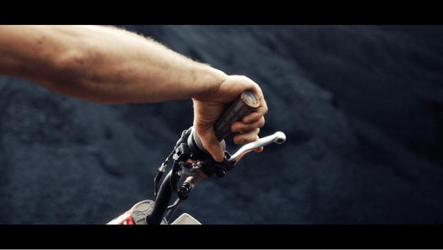 Detail of Sebastien's hand holding the handle-bar