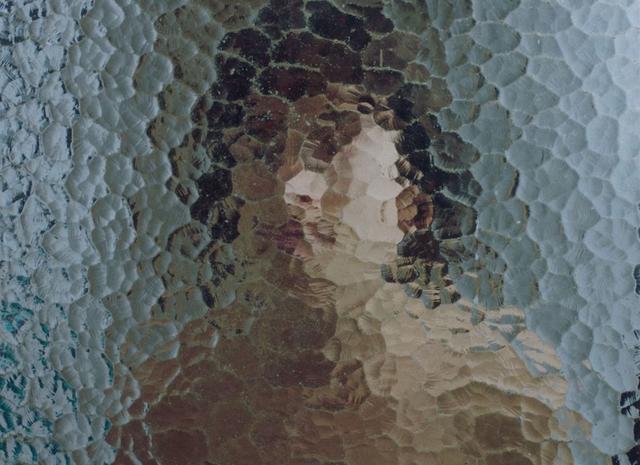 Laura Indigo behind a glass door