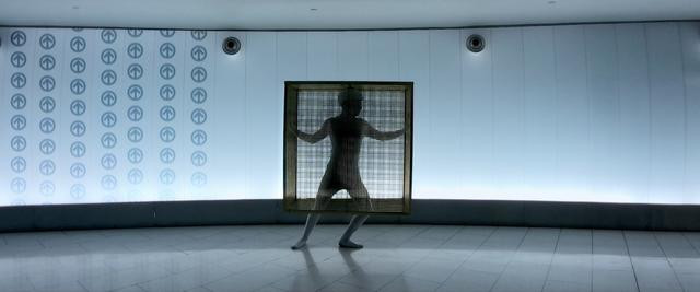 A person dancing in a golden cube cage in Montreal subway