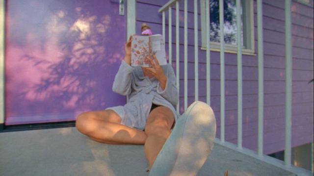 A girl sitting on the pink and white house porch and reading on a sunny summer afternoon