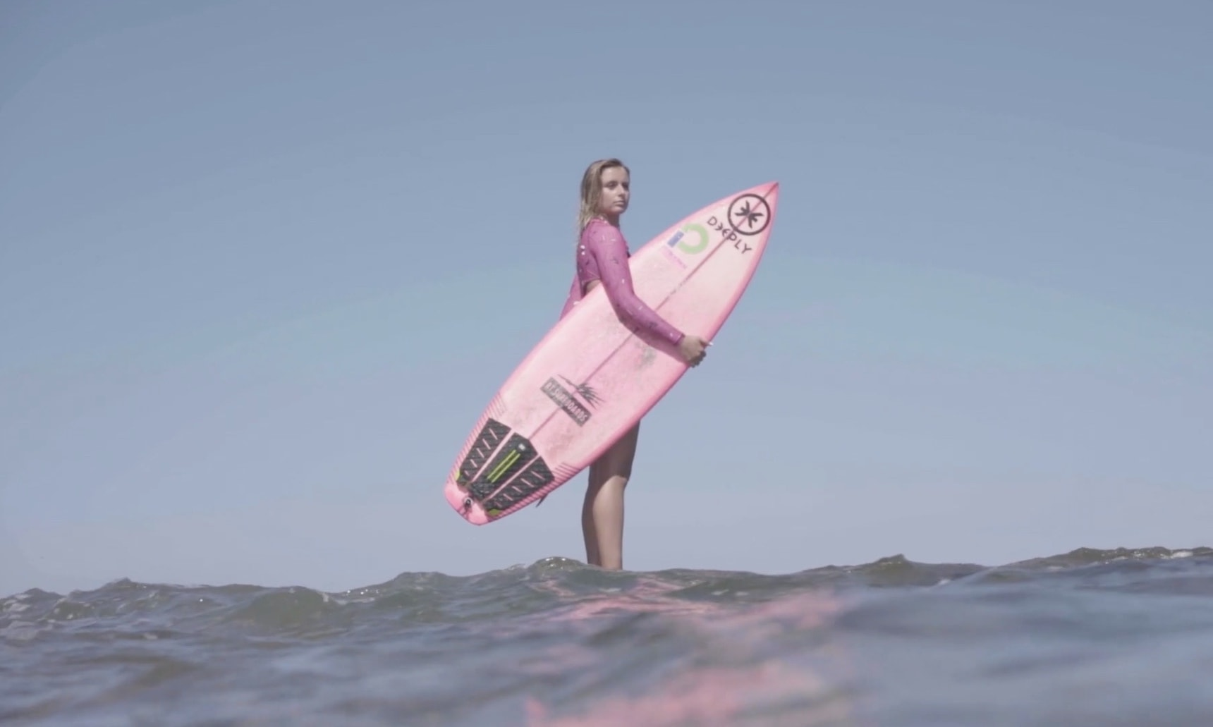 Uhaina Joly standing in the water holding her surfboard