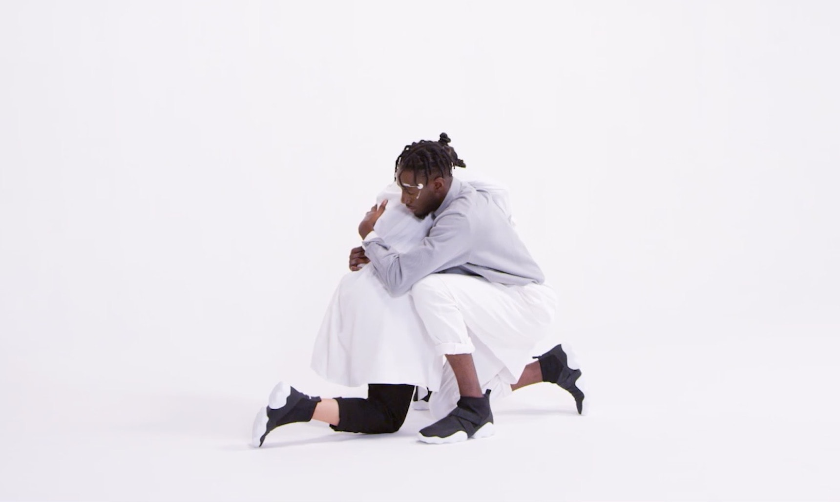 A black dancer duo hugging on white background