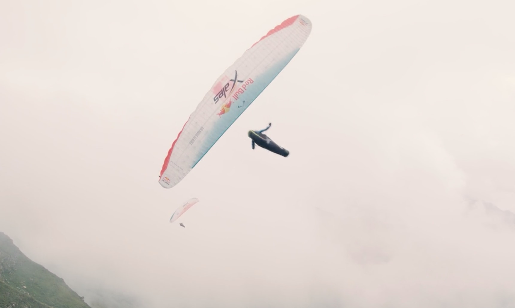 A paraglider flying through the misty sky