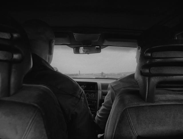 Two men sitting in the front of an old car