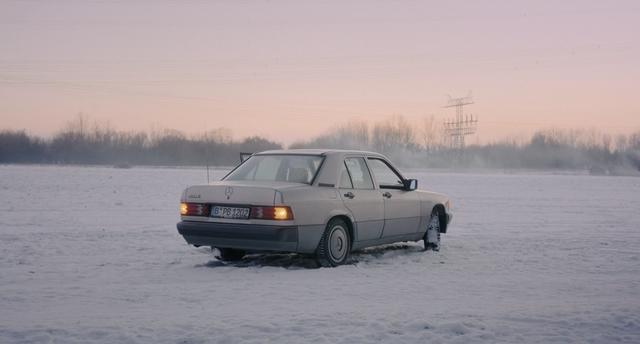 A Mercedez car on a snowy ground during sunset